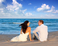 Couple in love sitting in blue beach Stock Image