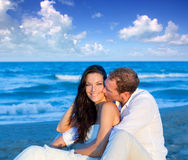 Couple in love sitting in blue beach Royalty Free Stock Photos
