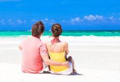 Couple in love sitting in blue beach on vacation Stock Photo