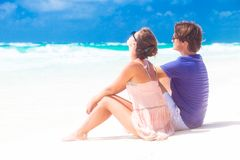 Couple in love sitting in blue beach on vacation Royalty Free Stock Photography