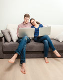 Couple in love sitting on couch and using two laptops Stock Photo