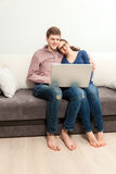 Couple in love sitting on couch and watching movie on laptop Stock Photography