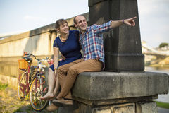Couple in love sitting on the curb embankment and passionately talking. Royalty Free Stock Photo