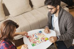 Couple playing ludo board game. Couple in love sitting on the floor next to a table, playing ludo board game and enjoying their free time together. Woman stock photos