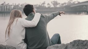 Couple in love sitting on the grass and hugging in a park. Against the background of a beautiful bay and a bridge. Pleasant evening near the ocean. Talking and stock video footage