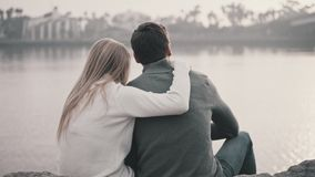 Couple in love sitting on the grass and hugging in a park. Against the background of a beautiful bay and a bridge. Pleasant evening near the ocean. Talking and stock footage