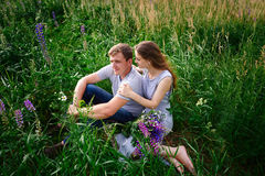 Couple in love sitting on green grass summer meadow Royalty Free Stock Photos