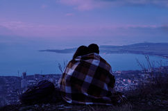 Couple in love sitting on hill above the city in night Stock Photos