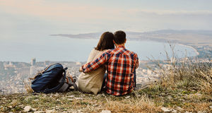 Couple in love sitting on hill and looking at the city Stock Photos