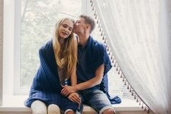 Couple in love sitting at home on the window. Tender loving embrace of newlyweds. Fun morning happy mood of a loving couple. Girl. Cuddles up to boyfriend stock images