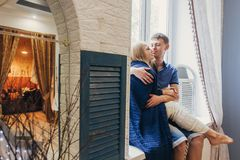 Couple in love sitting at home on the window. Tender loving embr Royalty Free Stock Photography