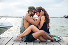 Couple in love sitting and kissing at wooden sea pier Royalty Free Stock Photography