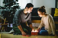 Couple in love sitting on a living room floor exchanging Christmas presents. Happy young couple in santa hats sitting with christmas presents on floor Royalty Free Stock Image