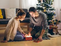Couple in love sitting on a living room floor exchanging Christmas presents. Happy young couple in santa hats sitting with christmas presents on floor Stock Image