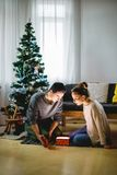Happy young couple in santa hats sitting with christmas presents on floor. Couple in love sitting on a living room floor exchanging Christmas presents and having Stock Photography