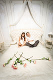 Couple in love sitting on luxurious bed decorated with roses Royalty Free Stock Photo