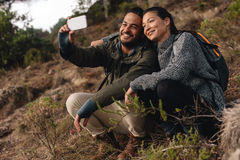 Couple in love sitting on mountain trail and taking selfie. Young men and women hiking in countryside and talking self portrait with mobile phone Royalty Free Stock Photography