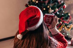 Couple in love sitting next to a Christmas tree, wearing Santa`s hat and hugging. Young people celebrating New year at home at royalty free stock photos