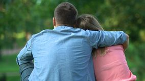 Couple in love sitting outdoor, guy tenderly embracing his girl, back-view stock footage