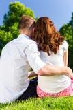 Couple in love sitting on park lawn enjoying sun Stock Photos
