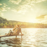 Couple in love sitting on the pier Stock Image