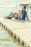 Couple in love sitting on the pier, embrace.  Stock Photography