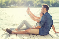 Couple in love sitting on the pier, selfie Stock Photos