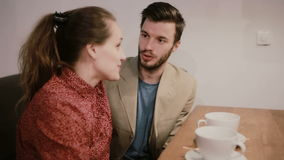 A couple in love sitting on a sofa at the table with empty coffee cups on it. They are talking and smiling. stock video footage