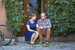 Couple in love sitting on the steps at the door of the house. Royalty Free Stock Photos