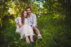 Couple in love sitting at summer park stock photos