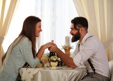 Couple in love  sitting at a table in restaurant holding hands Royalty Free Stock Photos