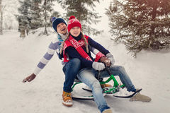 Couple in love sledding in the winter park. Dressed in knit hats, mittens and scarf Stock Photo