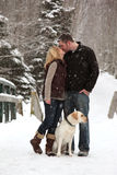 Couple in love in snow. A young couple kiss in the snow with their dog royalty free stock photo