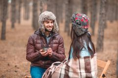 Couple in love, spend time sitting in the autumn forest, cute communicate and drink fragrant tea. Royalty Free Stock Images