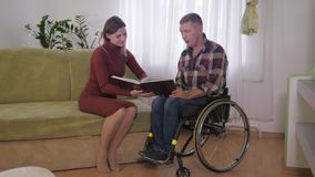 Couple in love spends time together, young wife and her husband in wheelchair read interesting stories in room stock footage