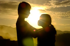 Couple of love stand and hug and eye contact each other in fog on the mountain at the morning and sunrise behind them. Silhouette and flare side view royalty free stock photos