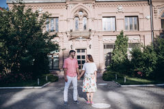 Couple in love stand in the old city.Old building and green trees on the background.Couple holding hands and looking at each other Royalty Free Stock Photos