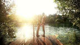 Couple in love standing on the dock holding hands by the river at sunset. Beautiful couple in love standing on the dock holding hands by the Mreznica river at stock video footage