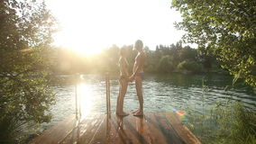 Couple in love standing on the dock holding hands by the river at sunset stock video