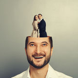 Couple in love standing in the man's head. Happy young businessman with open head. couple in love standing in the man's head. photo over grey background Royalty Free Stock Image