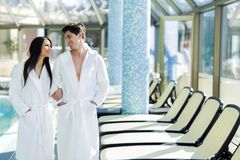 Couple in love standing next to a pool in a  robe. Couple in love standing next to a  pool in a  robe and relaxing Stock Image
