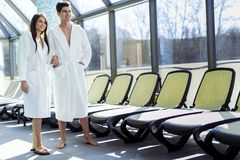 Couple in love standing next to a pool in a  robe. Couple in love standing next to a  pool in a  robe and relaxing Stock Images