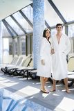Couple in love standing next to a pool in a  robe. Couple in love standing next to a  pool in a  robe and relaxing Royalty Free Stock Photos