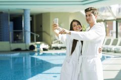Couple in love standing next to a  pool in a  robe. And relaxing Royalty Free Stock Photo