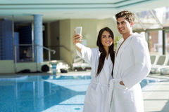 Couple in love standing next to a  pool in a  robe. And relaxing Royalty Free Stock Images