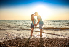 Couple in love standing in water and kissing Stock Photos