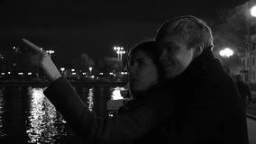 A couple in love stands against the lights of a night city at waterfront. Amazing wedding couple near the river at night. Monochrome stock video footage