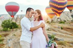 Couple in love stands on background of balloons in Cappadocia. Man and a woman on hill look at a large number of flying balloons Royalty Free Stock Images