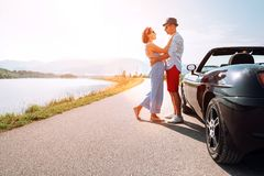 Couple in love stands near the cabriolet car on the picturesque Stock Images