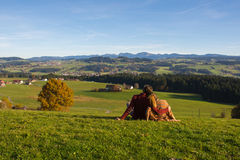 Couple in love stays on green grass looking at hills and mountains in autumn , sourrounded by beautiful rural landscape from Allga Stock Photos